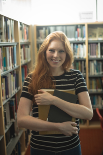 Beautiful woman holding books in libraryの写真素材 [FYI02240687]