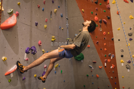 Male athlete looking up while climbing wall in gymの写真素材 [FYI02240748]