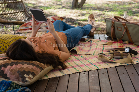 Woman using tablet in tentの写真素材 [FYI02240762]