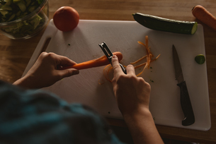 Girl standing in kitchen peeling carrot with peeler at homeの写真素材 [FYI02240784]