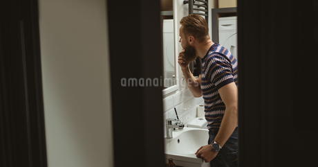 Man checking out himself in mirrorの写真素材 [FYI02240819]