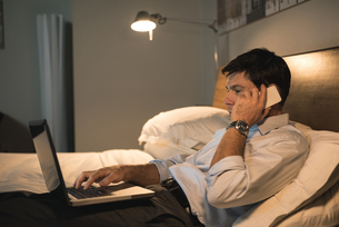 Businessman using laptop while talking on mobile phoneの写真素材 [FYI02240829]