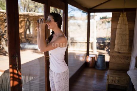 Beautiful woman looking through binoculars from windowの写真素材 [FYI02240849]