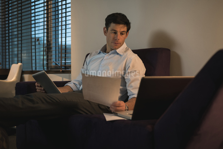Business man verifying documents while using digital tabletの写真素材 [FYI02240932]