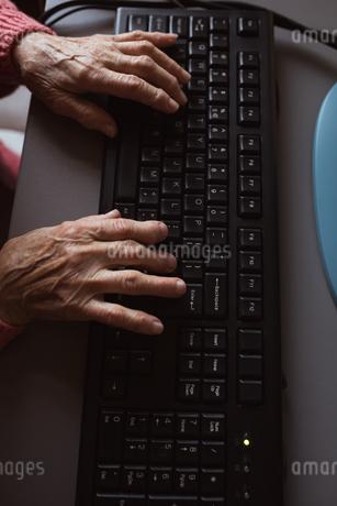 Senior woman tying on keyboardの写真素材 [FYI02240933]