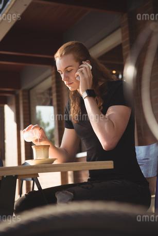 Man talking on mobile phone while having coffeeの写真素材 [FYI02240935]