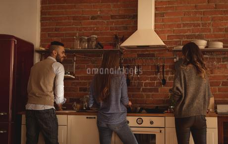 Friends preparing food in kitchenの写真素材 [FYI02240963]