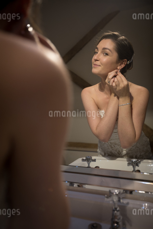 Smiling bride wearing earrings in front of the mirrorの写真素材 [FYI02240964]