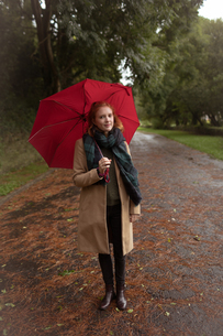 Woman standing with umbrella in the parkの写真素材 [FYI02240987]