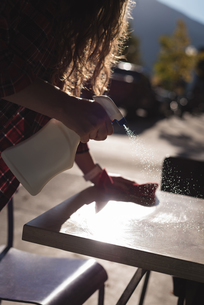 Woman spraying water while cleaning tableの写真素材 [FYI02240992]