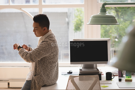 Executive sitting on desk checking time in his smartwatchの写真素材 [FYI02240999]