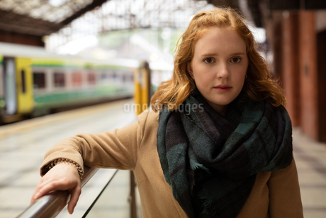 Young woman standing at railway platformの写真素材 [FYI02241009]