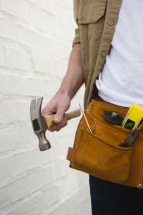 Male carpenter with tool belt holding hammerの写真素材 [FYI02241044]