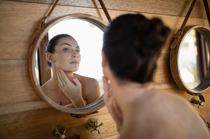 Woman looking at mirror in cottageの写真素材 [FYI02241079]
