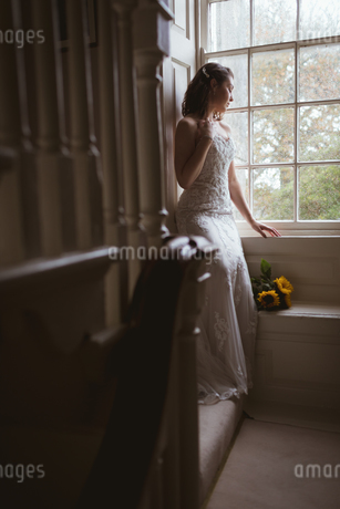 Bride looking out of the windowの写真素材 [FYI02241101]