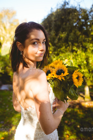 Beautiful bride holding a sunflower bouquet in the gardenの写真素材 [FYI02241110]