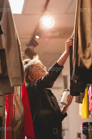 Beautiful woman selecting clothes from rackの写真素材 [FYI02241131]