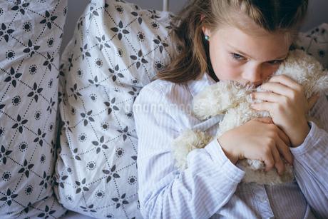 Girl holding teddy bear on bedの写真素材 [FYI02241150]