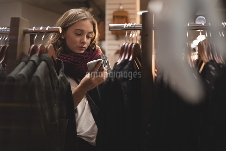 Beautiful woman using mobile phone while shoppingの写真素材 [FYI02241153]