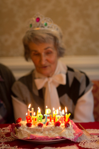 Senior woman blowing out candles on birthday cakeの写真素材 [FYI02241155]