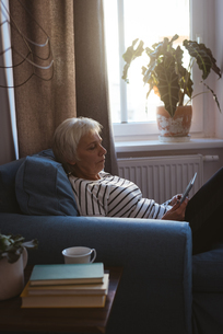 Senior woman sitting on sofa using her tablet in living roomの写真素材 [FYI02241167]
