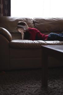 Boy using digital tablet with headphones in living roomの写真素材 [FYI02241180]