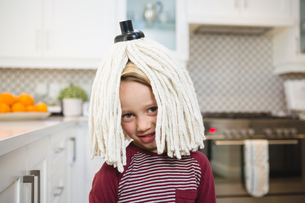 Happy boy with mop on head in kitchenの写真素材 [FYI02241185]