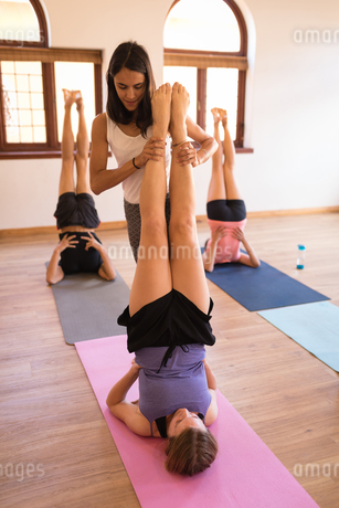 Female trainer assisting woman in yoga exerciseの写真素材 [FYI02241187]