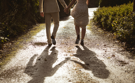 Bride and groom walking hand in hand in the gardenの写真素材 [FYI02241193]