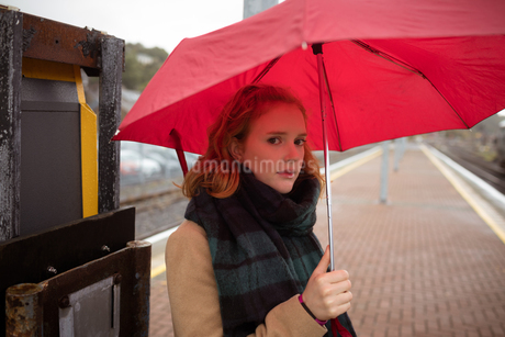 Young woman with umbrella waiting for train on platformの写真素材 [FYI02241252]
