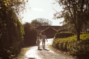 Bride and groom walking hand in hand in the gardenの写真素材 [FYI02241259]