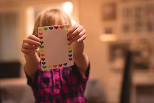 Girl holding heart shape valentine cardの写真素材 [FYI02241278]