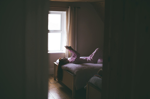 Woman using mobile while lying on bed in bedroomの写真素材 [FYI02241289]