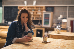 Woman using mobile phone in cafeの写真素材 [FYI02241294]