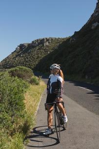 Female biker standing with mountain bike on roadの写真素材 [FYI02241299]