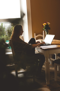 Woman using laptop at homeの写真素材 [FYI02241360]