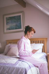 Woman using digital tablet on bed in bedroomの写真素材 [FYI02241362]