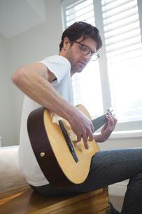 Man playing guitar in bedroomの写真素材 [FYI02241380]