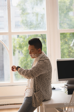 Executive sitting on desk checking time in his smartwatchの写真素材 [FYI02241411]