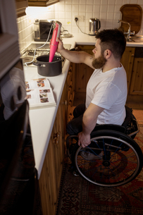 Disabled man repairing a pan in kitchenの写真素材 [FYI02241413]