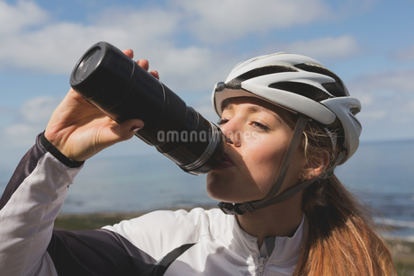 Female biker drinking water from bottle on a sunnyの写真素材 [FYI02241425]