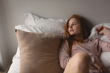 Woman relaxing on bed in bedroom at homeの写真素材 [FYI02241439]