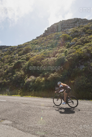 Biker riding mountain bike on roadの写真素材 [FYI02241470]