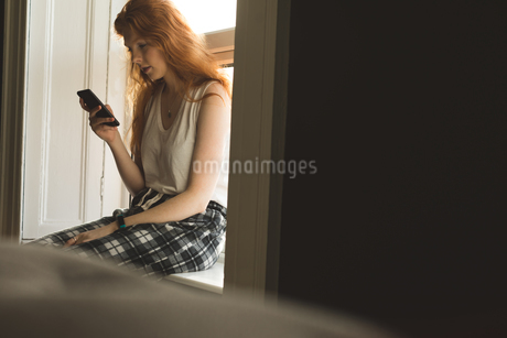Woman using mobile phone at homeの写真素材 [FYI02241485]