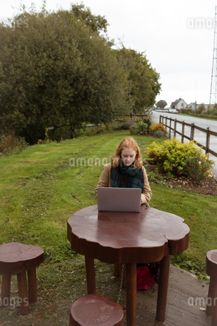 Woman using laptop in the parkの写真素材 [FYI02241489]