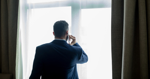 Businessman talking on mobile phone in hotel roomの写真素材 [FYI02241497]