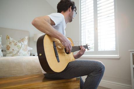 Man playing guitar in bedroomの写真素材 [FYI02241518]