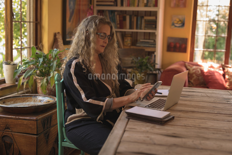 Mature woman sitting on chair and using her smart phoneの写真素材 [FYI02241522]