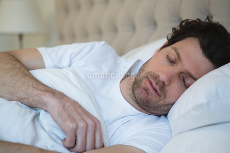 Man sleeping in bedroomの写真素材 [FYI02241533]