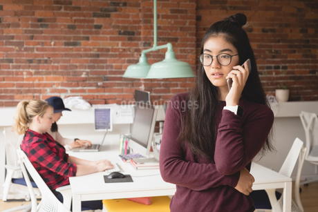 Female executive talking on mobile phone while colleagues working in backgroundの写真素材 [FYI02241556]